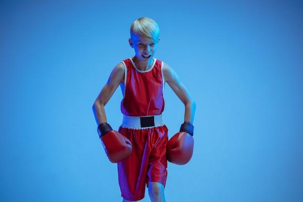 Adolescent En Boxe Sportswear Isolé Sur Fond Bleu Studio En Néon. Boxeur Caucasien Masculin Novice S'entraînant Dur Et Travaillant, Coups De Pied. Sport, Mode De Vie Sain, Concept De Mouvement. Photo gratuit