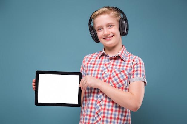 Adolescent avec un casque montre l'écran du smartphone, photo avec espace pour le texte Photo Premium
