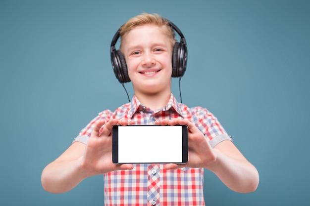 Adolescent avec un casque montre l'écran du smartphone Photo Premium