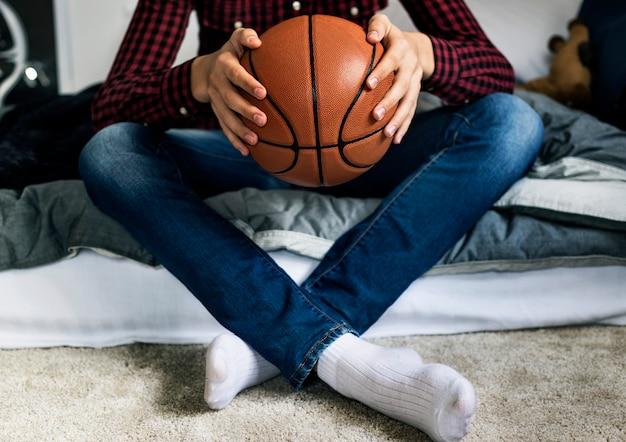 Adolescent Dans Une Chambre à Coucher Tenant Un Concept D'aspiration Et De Solitude De Basket-ball Hobby Photo Premium