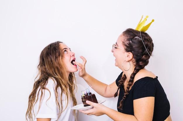 Adolescent donnant un gâteau au chocolat à son amie Photo gratuit
