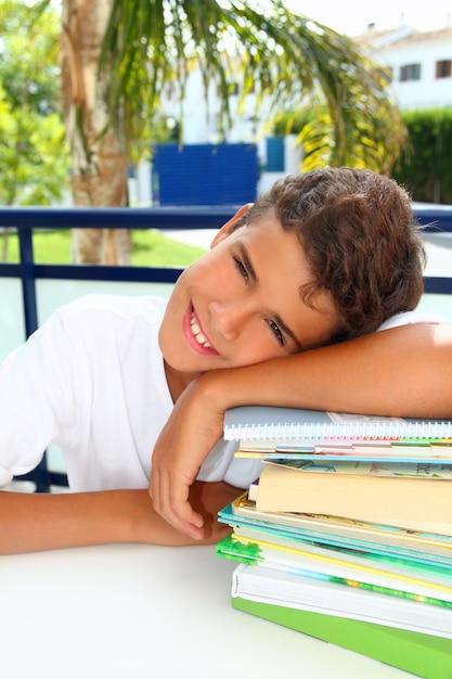 Adolescent étudiant garçon heureux de penser avec des livres Photo Premium