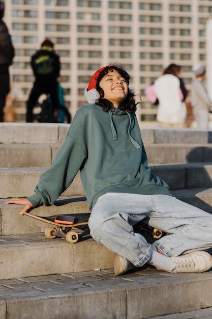 Adolescent à L'extérieur Appréciant La Musique Au Casque Alors Qu'il était Assis Sur Une Planche à Roulettes Photo gratuit