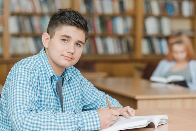 Adolescent, Faire Ses Devoirs Dans La Bibliothèque Photo gratuit