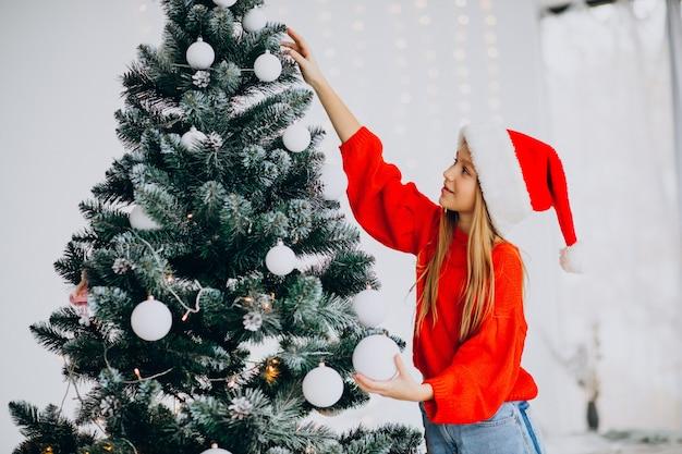 Adolescent Fille Mignonne En Bonnet De Noel Rouge Par Arbre De Noël Photo gratuit