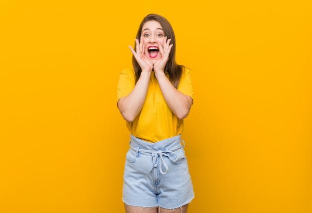 Adolescent De Jeune Femme Vêtu D'une Chemise Jaune Criant Excité à L'avant. Photo Premium