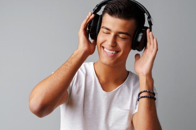 Adolescent jeune homme, écouter de la musique avec ses écouteurs sur un fond gris Photo Premium