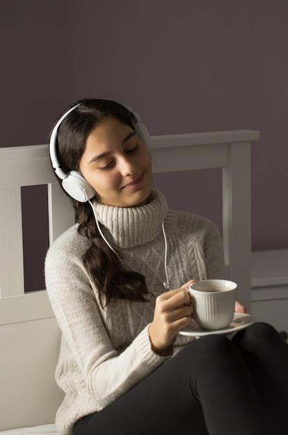 Adolescent Sur Le Lit écoutant De La Musique Avec Des écouteurs Et Une Tasse De Thé Photo Premium