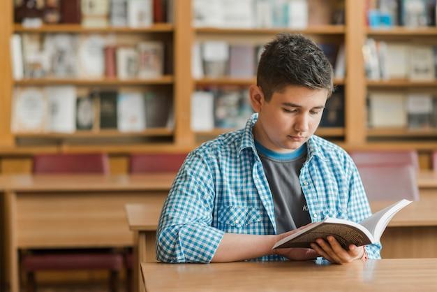 Adolescent, Livre De Lecture Dans La Bibliothèque Photo gratuit