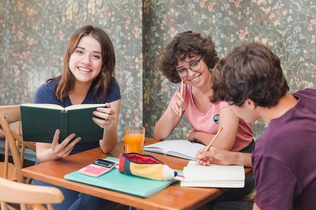 Adolescent avec livre près d'étudier des amis Photo gratuit