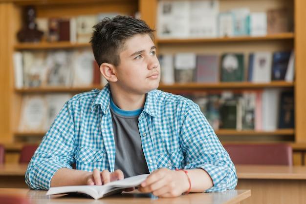 Adolescent Avec Livre En Regardant Loin Photo gratuit
