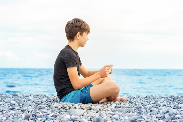Adolescent mignon assis sur la plage et regardant la mer Photo Premium