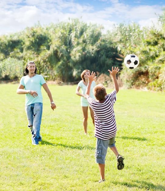 Un adolescent et des parents heureux jouent au football Photo gratuit