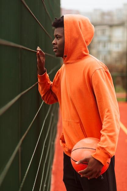 Adolescent Posant Sur Le Terrain De Basket Photo gratuit