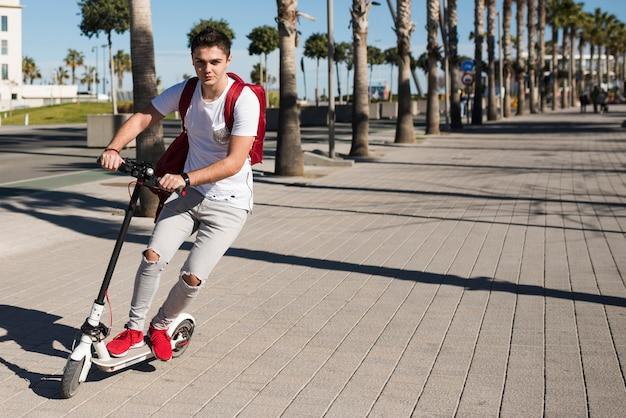 Adolescent avec scooter Photo gratuit