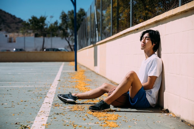 Adolescent se détendant au terrain de basket Photo gratuit