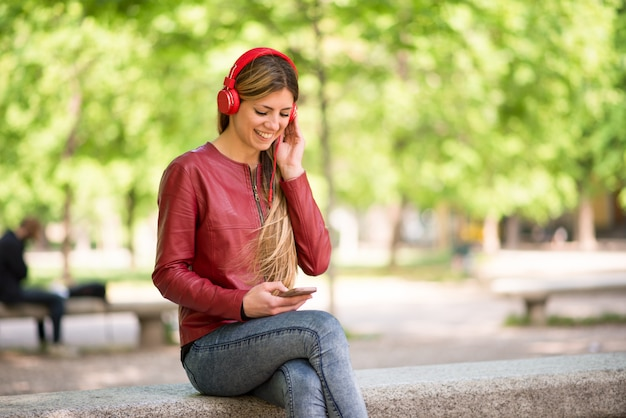 Adolescent souriant écoute de la musique depuis un téléphone Photo Premium