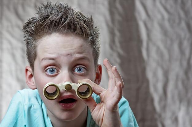 Adolescent surpris en regardant émotionnellement à travers des jumelles Photo Premium