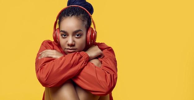 Adolescente africaine avec des dreadlocks en musique coupe-vent rouge Photo Premium