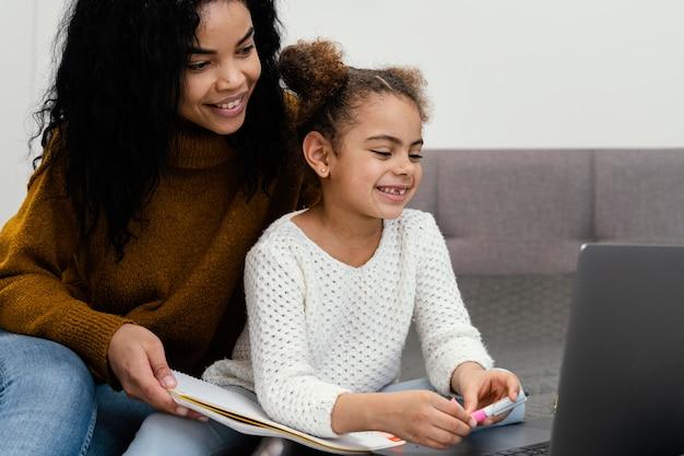 Adolescente Aidant Sa Soeur à L'aide D'un Ordinateur Portable Pour L'école En Ligne Photo gratuit