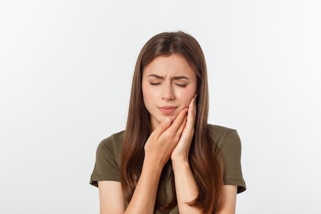 Adolescente appuyant sur sa joue meurtrie avec une expression douloureuse comme si elle avait un terrible mal de dents Photo Premium