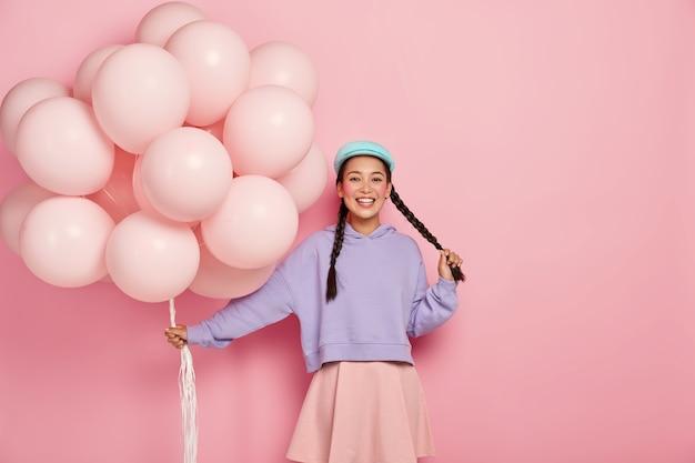 Une Adolescente Asiatique Assez Joyeuse Vient En Vacances Avec Un Tas De Ballons à Air, A Deux Longues Tresses Sombres, Des Joues Rouges Et Un Maquillage Minimal, Porte Un Pull Et Une Jupe Violets Surdimensionnés, étant De Bonne Humeur Photo gratuit