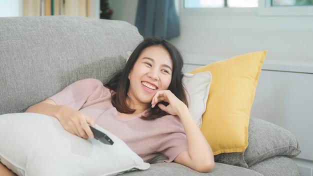 Adolescente asiatique jeune femme regardant la télévision à la maison, femme se sentir heureuse allongée sur un canapé dans le salon. femme de mode de vie se détendre au matin à la maison concept. Photo gratuit