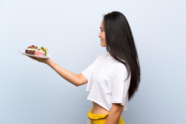 Adolescente asiatique tenant beaucoup de mini gâteaux différents avec une expression heureuse Photo Premium