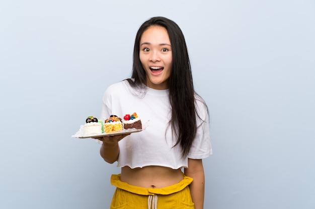 Adolescente asiatique tenant plein de mini gâteaux différents avec une expression du visage surprise et choquée Photo Premium