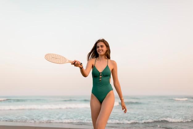 Adolescente en bikini vert jouant avec tennis au bord de la mer Photo gratuit
