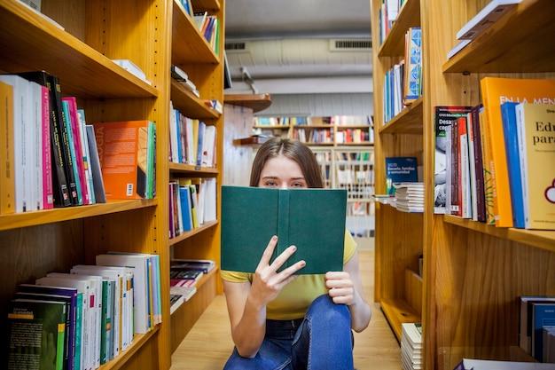 Adolescente Couvrant Le Visage Avec Un Livre Photo gratuit