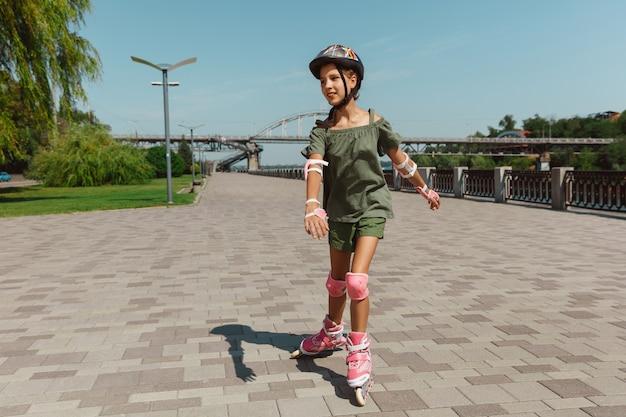 Adolescente Dans Un Casque Apprend à Monter Sur Des Patins à Roulettes à L'extérieur Photo gratuit