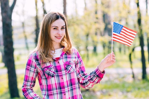 Adolescente avec drapeau usa à la main Photo gratuit