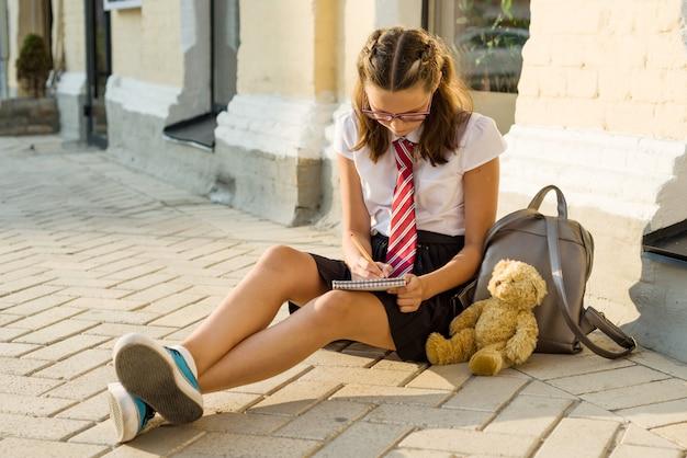 Une adolescente d'écolière écrit dans un cahier. journal de filles, secrets, premier amour Photo Premium