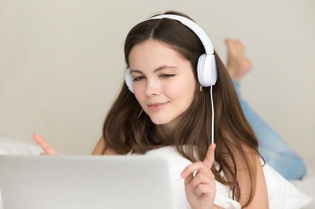 Une adolescente écoute choisir et acheter des chansons en ligne Photo gratuit