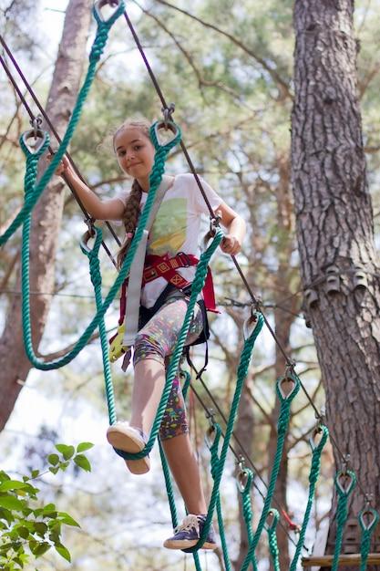 Adolescente avec équipement d'escalade dans un parc d'attractions de corde Photo Premium