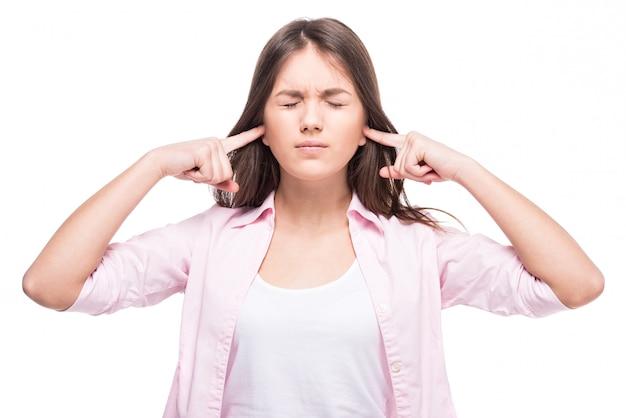 Une adolescente a fermé ses oreilles avec ses doigts. Photo Premium