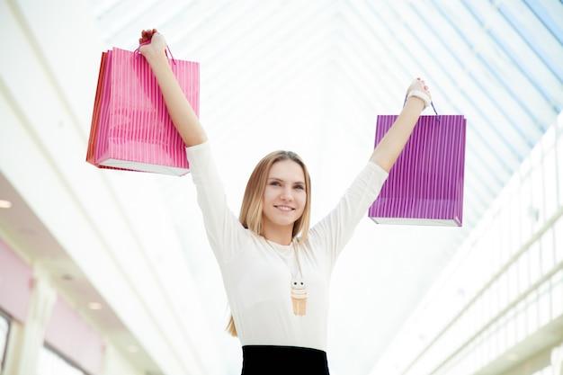 Une adolescente heureuse satisfaite de ses achats portant des sacs à provisions roses Photo gratuit