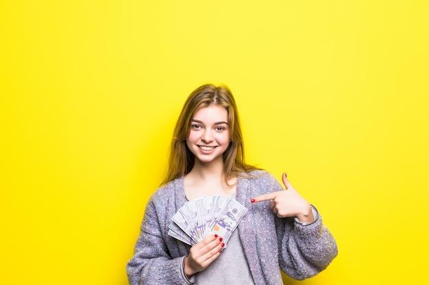 Adolescente Joyeuse Avec Des Dollars Dans Ses Mains Pointé Sur Eux Isolés Photo gratuit