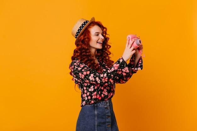 Une Adolescente En Jupe En Jean Et Chemisier élégant Fait Joyeusement La Photo, Tenant Une Mini Caméra Sur L'espace Orange. Photo gratuit