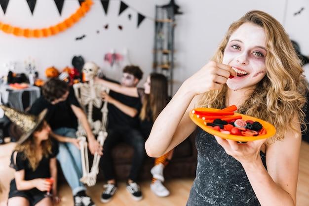 Adolescente avec le maquillage de zombie et la plaque orange mangeant de la marmelade Photo gratuit