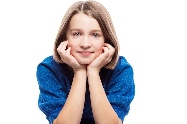 Adolescente Mignonne Dans Un Pull Bleu Sourit. Isolé Sur Fond Blanc. Photo Premium