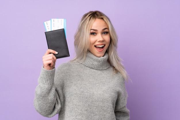 Adolescente Sur Mur Violet Isolé Heureux En Vacances Avec Passeport Et Billets D'avion Photo Premium