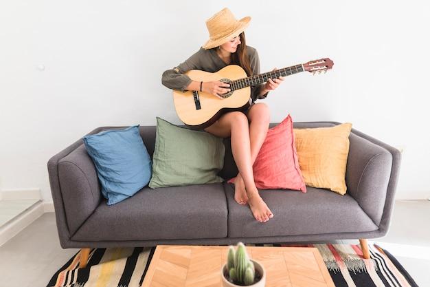 Adolescente, porter, chapeau, jouer guitare, chez soi Photo gratuit