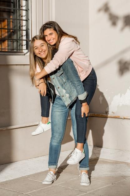 Adolescente qui donne à sa petite amie une promenade en ferroutage debout devant le mur Photo gratuit
