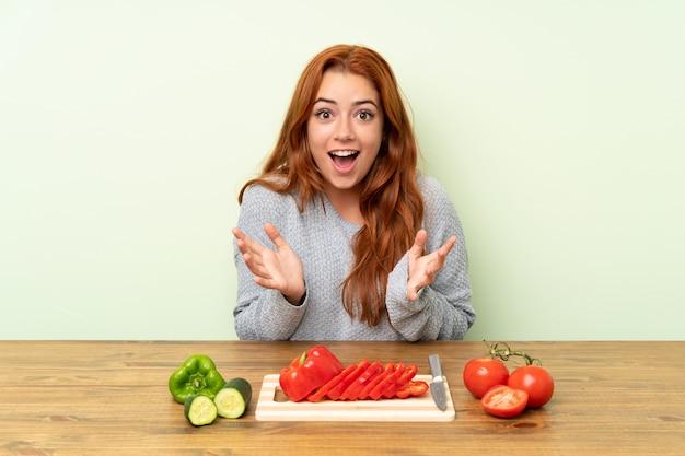 Adolescente rousse avec des légumes dans un tableau avec une expression faciale surprise Photo Premium