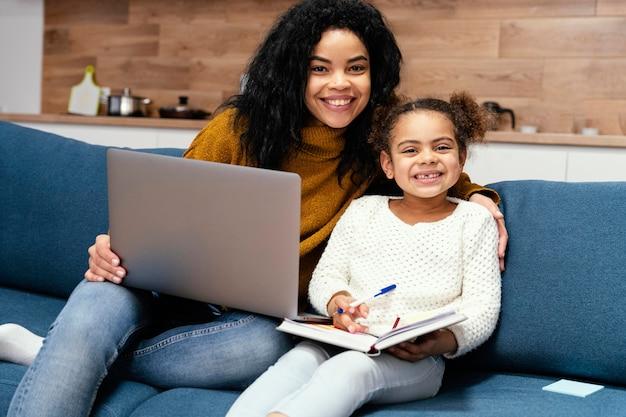 Adolescente Smiley Aidant La Petite Soeur Avec L'école En Ligne Sur Ordinateur Portable Photo gratuit