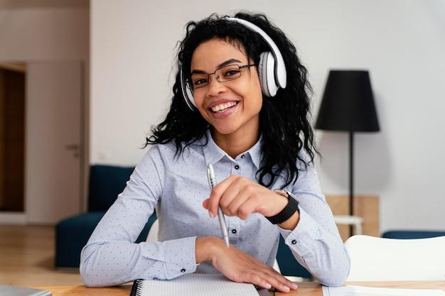 Adolescente Smiley à La Maison Pendant L'école En Ligne Avec Des écouteurs Photo Premium