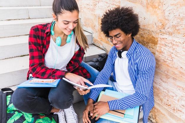 Adolescente souriante montrant quelque chose sur un livre à son amie Photo gratuit
