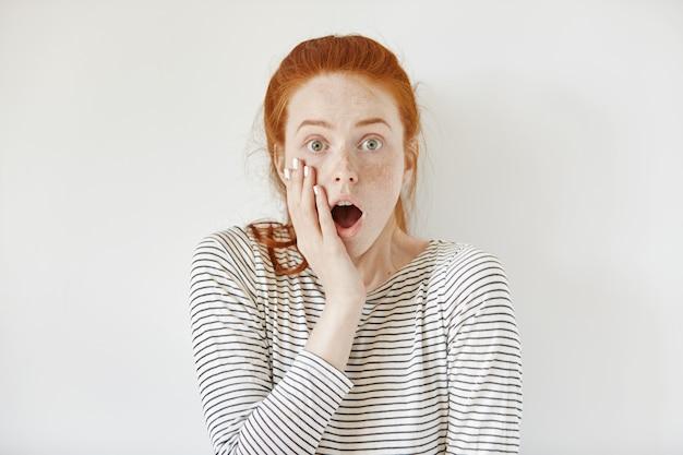 Adolescente Surprise, étonnée, Portant Une Chemise De Marin Touchant Sa Joue Et Gardant La Bouche Grande Ouverte, Choquée Par Des Nouvelles Inattendues. Oublieuse Jeune Femme à La Peur Et Peur Photo gratuit